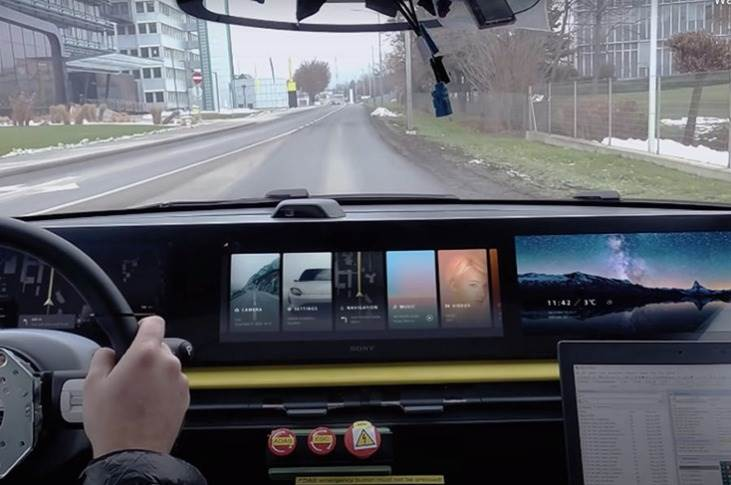 Fully functioning infotainment display spans the width of the dashboard, with the central display showing a detailed digital rendering of the car