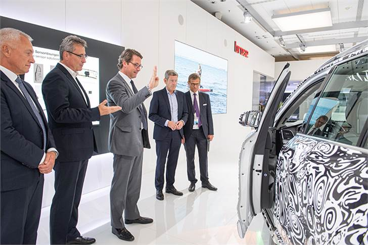 German Minister of Transport Andreas Scheuer (centre) opens the driver door of the Brose Concept Car with a hand gesture.