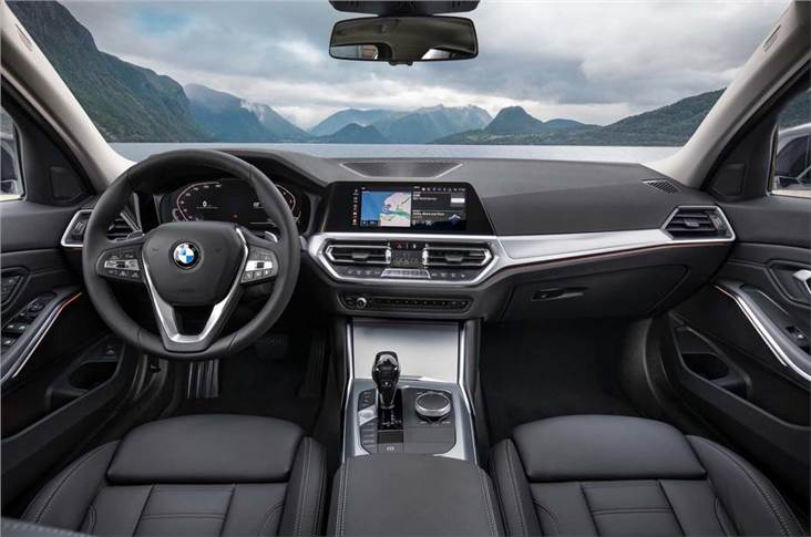 The iDrive controller sits aft of cupholders. Space is virtually unchanged, despite the car's extra length