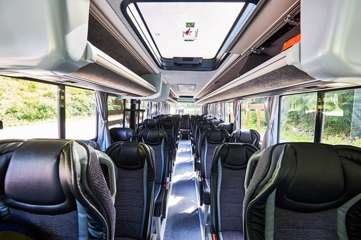 Premium seating arrangement in the buses with storage space above the seat, similar to flights.