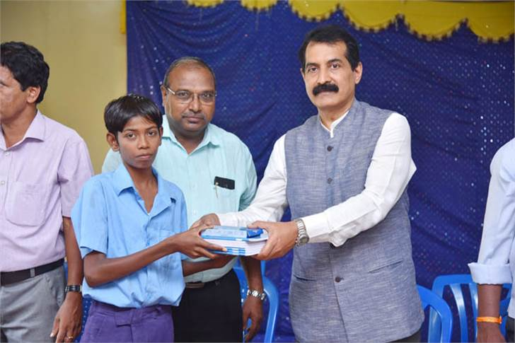K V Rajendra Hegde, GM, TKM, hands over books and bags to students. Also seen are Gangemare Gowda, deputy director of Public Instruction and Marilinge Gowda, Block Education Officer, Ramanagara.