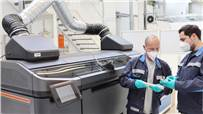 Two Volkswagen staffers check the quality of structural parts produced using the binder jetting process for car production in front of the prototype of the special printer in Wolfsburg.