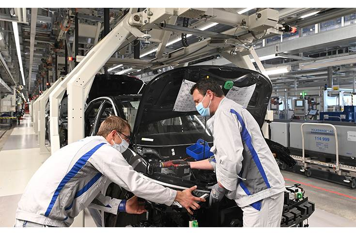Two employees at Volkswagen plant in Zwickau install the headlight on the ID.3.