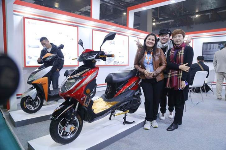 Lana Zou, Chief Operating Officer, Dao EVTech (on the right) and her team with the e-scooters displayed at the EV Expo in New Delhi.