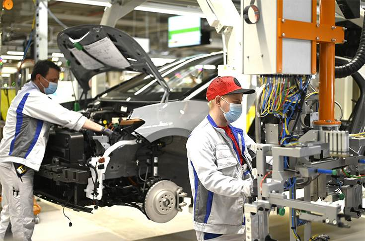 Two employees at Volkswagen in Zwickau install the front end on the ID.3.