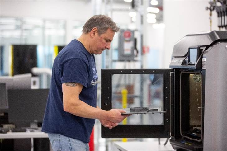 Dave Jacek, 3D printing technician, unloads 3D printed medical face shield parts at Ford's Advanced Manufacturing Center.