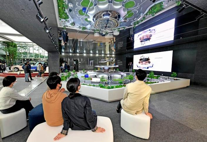 Hyundai Motor employees view a miniature model of smart mobility solutions, including UAM, PBV and Hub, for a dynamic human-centered future city concept, displayed in the first-floor lobby of its headquarters.